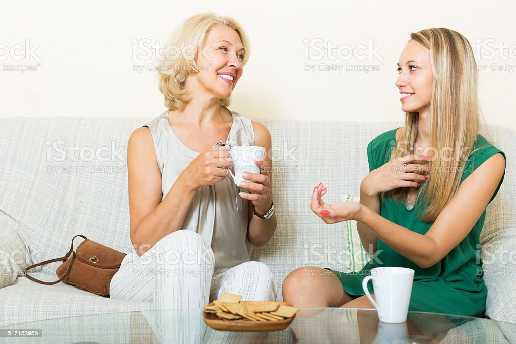 Mother and adult daughter on sofa stock photo