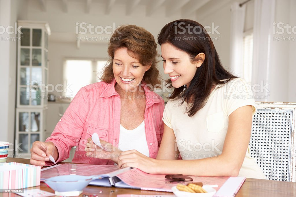 Mother and adult daughter scrapbooking and eating biscuits royalty-free stock photo
