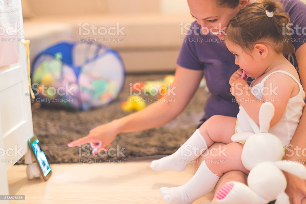 mother and baby are watching at phone stock photo