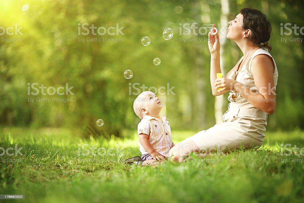 Mother and baby blowing bubbles stock photo