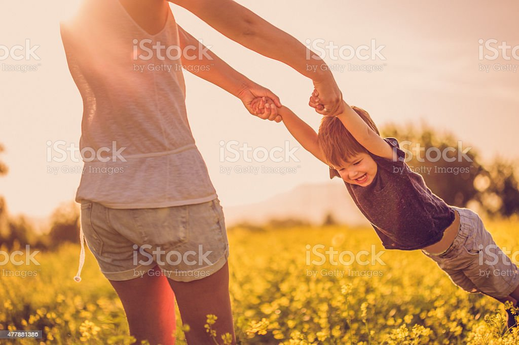Mother and baby boy having fun at the field stock photo