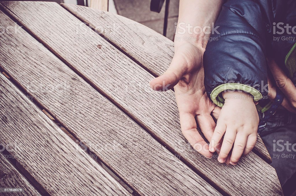 Mother and baby child holding hands on wooden table background stock photo