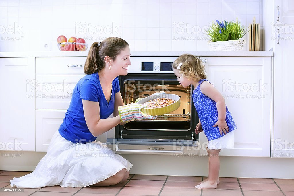 Mother and baby daughter baking a pie stock photo