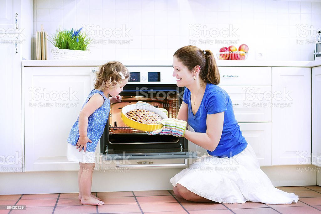 Mother and baby daughter cooking a pie stock photo