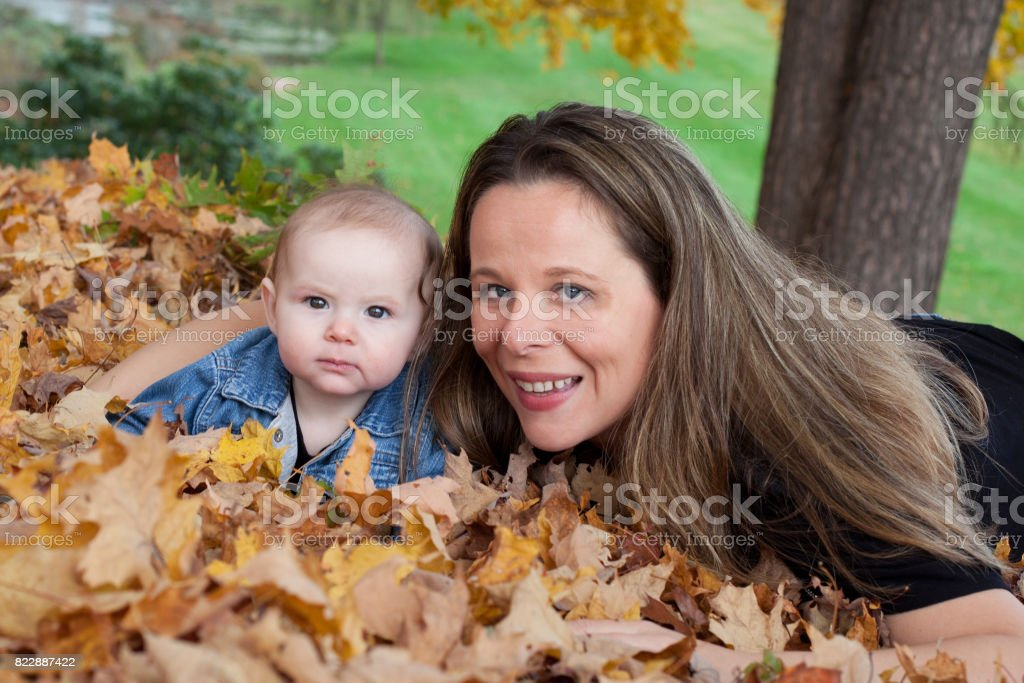 Mother and baby daughter in Autumn Leaves stock photo