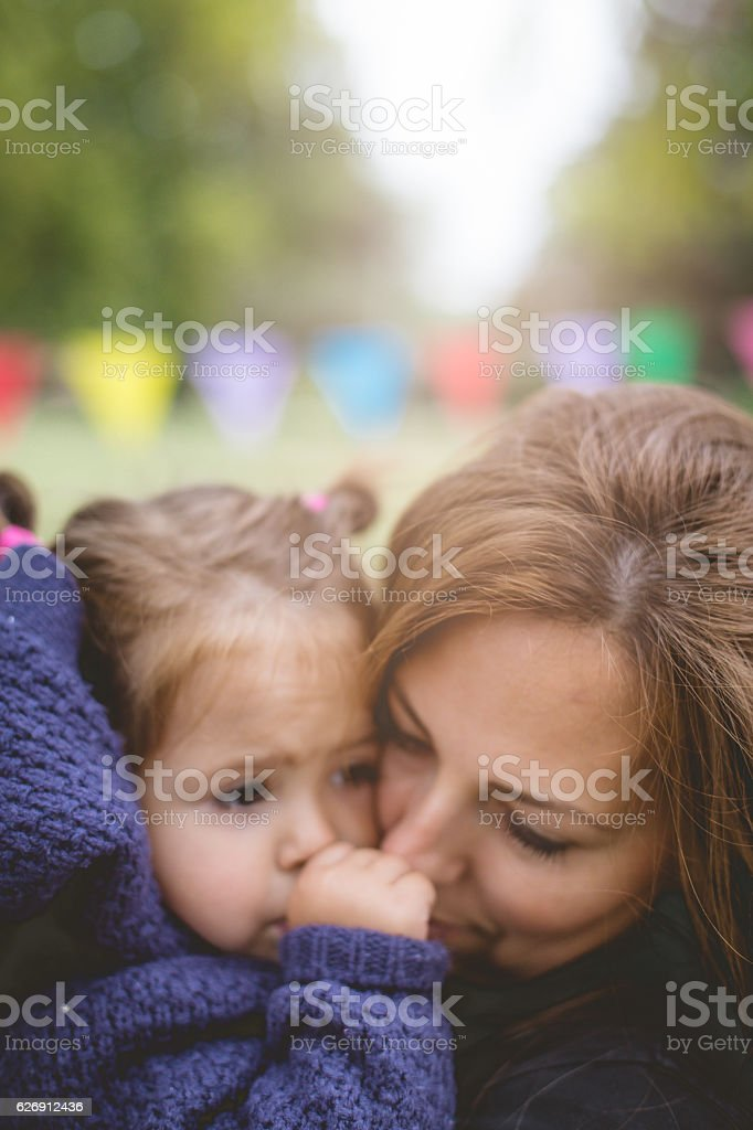 mother and baby embracing outside on a party stock photo