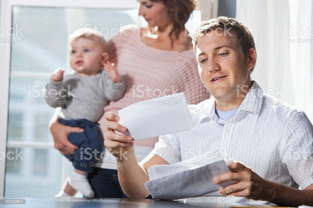 Mother and baby, father paying bills stock photo