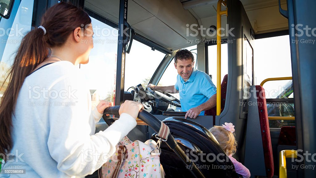 Mother and Baby Getting on Bus stock photo