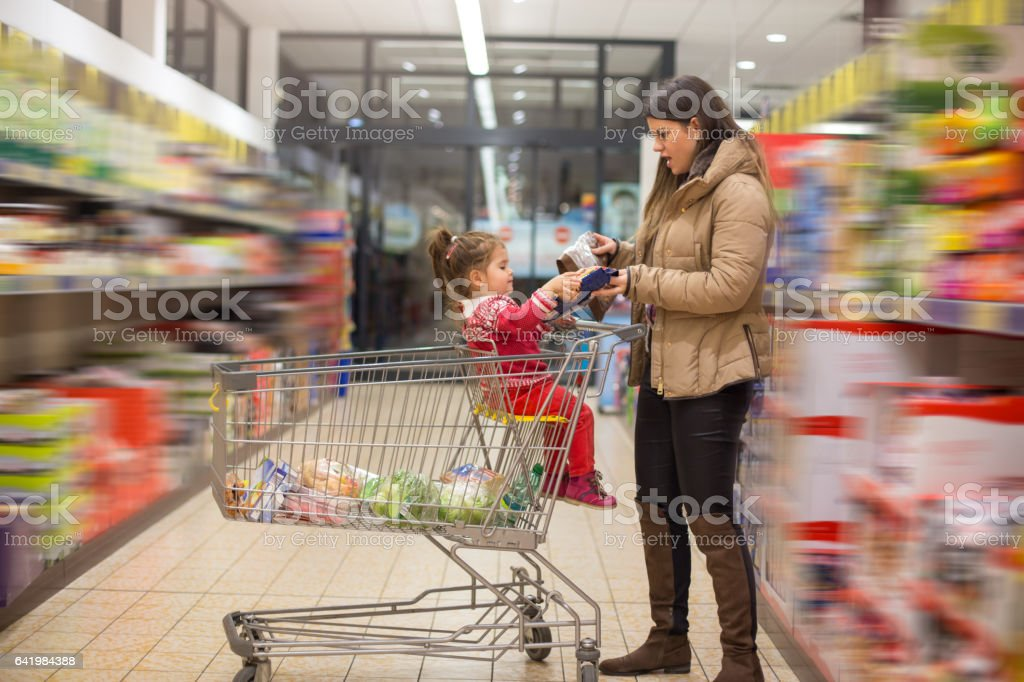 Mother and baby girl in grocery shopping stock photo