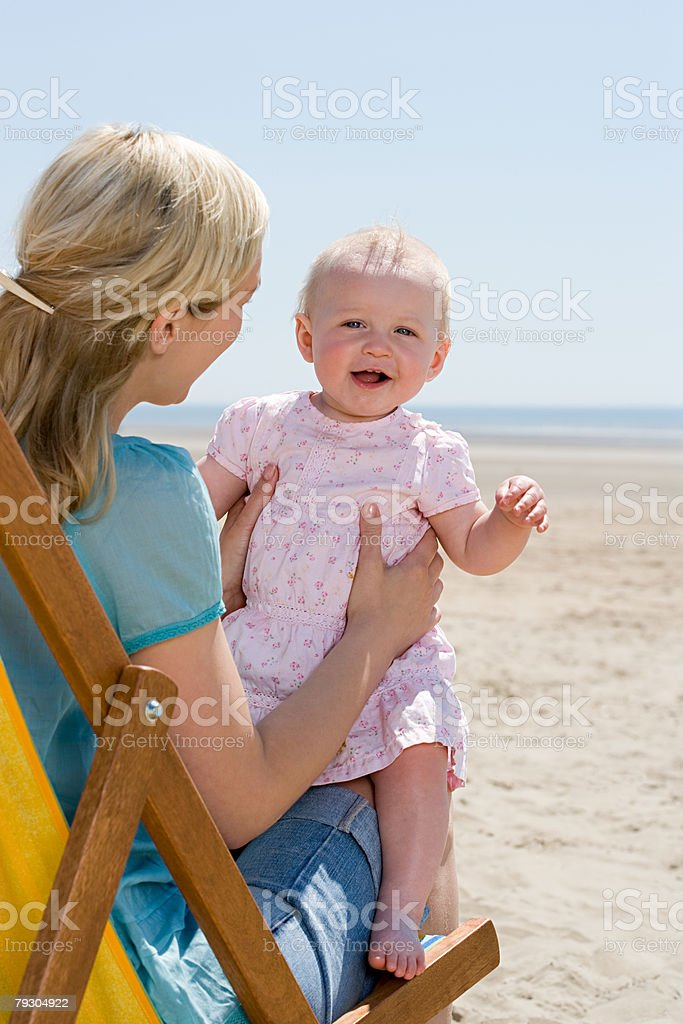 Mother and baby girl on a beach stock photo