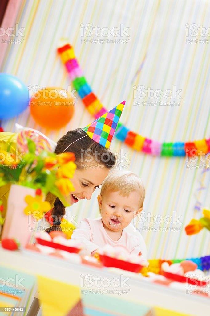 mother and baby having fun at birthday party stock photo