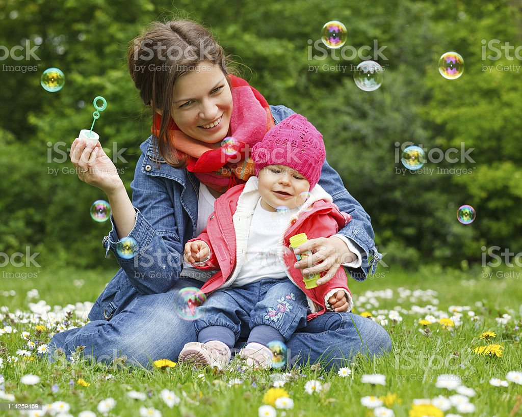 Mother and baby in the park playing with bubbles stock photo