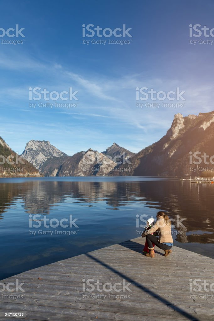 Mother and baby on a lake looking at mountains stock photo