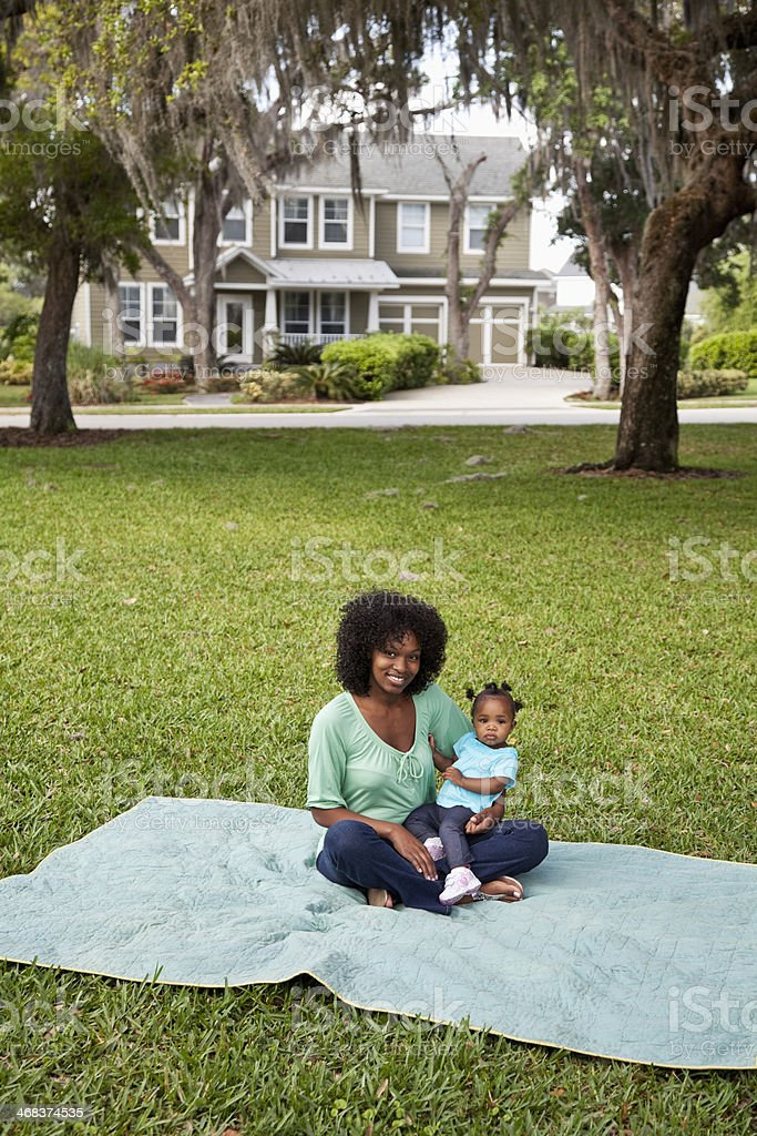 Mother and baby playing on picnic blanket stock photo