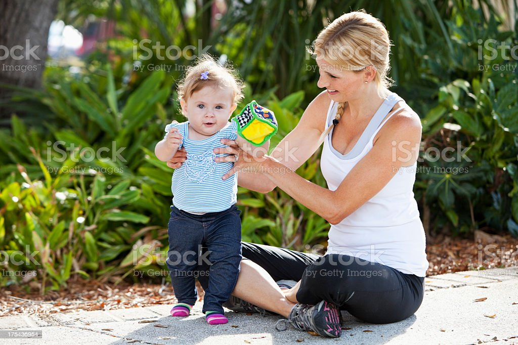 Mother and baby playing outdoors stock photo