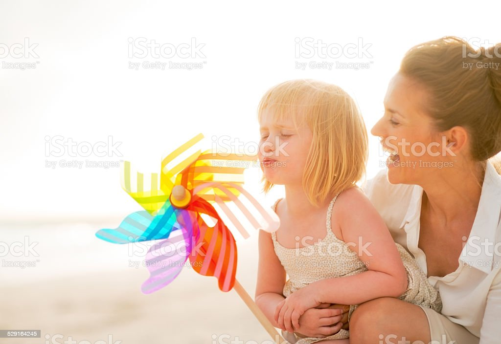 Mother and baby playing with windmill toy on the beach stock photo