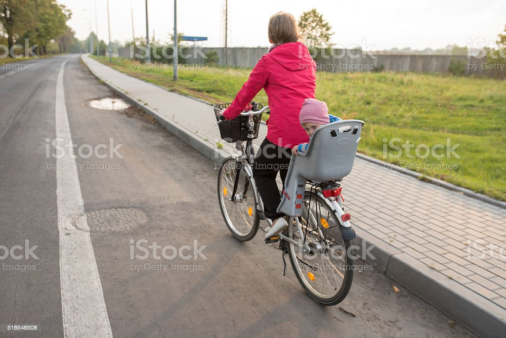 Mother and baby riding a bicycle stock photo