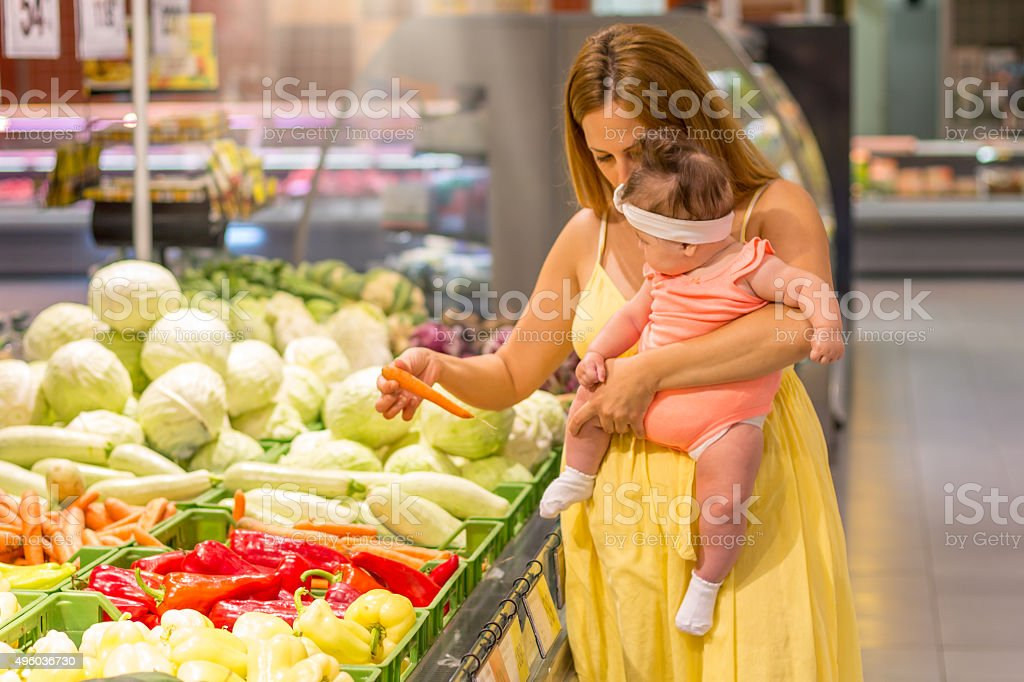 Mother and baby shopping groceries - carrot stock photo