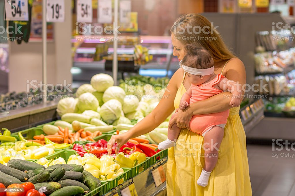 Mother and baby shopping groceries stock photo