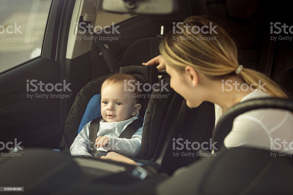 Mother and baby sitting in car on front seats stock photo