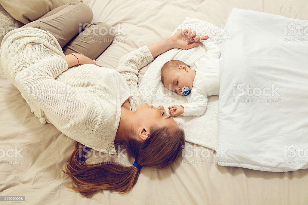 Mother and baby sleeping on the bed. stock photo