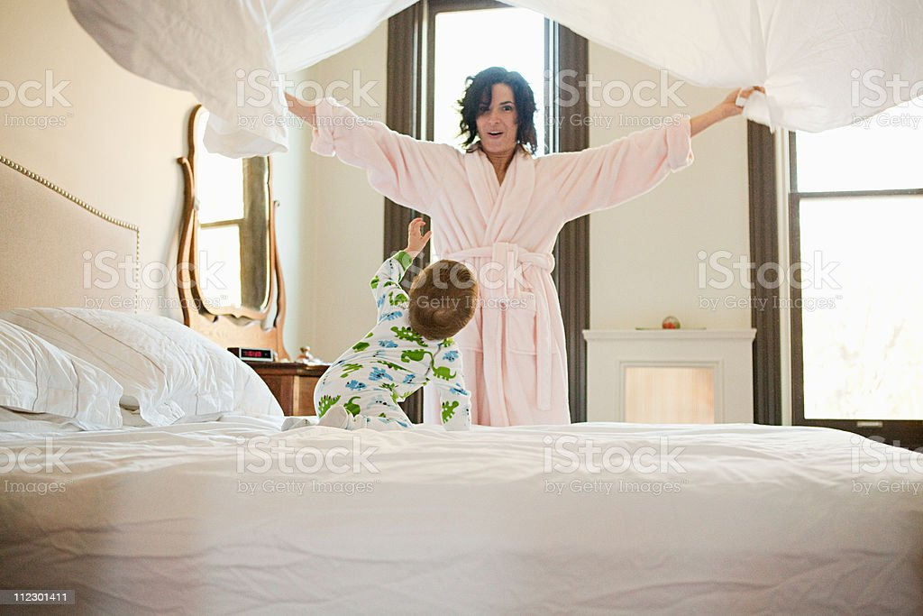 Mother and baby son making bed stock photo