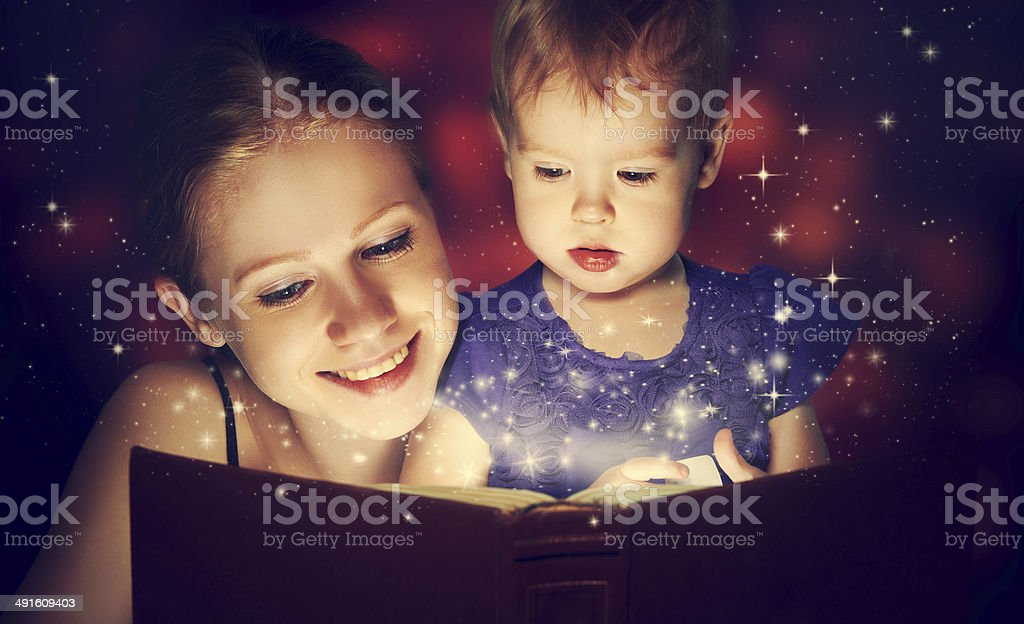 mother and child baby daughter reading magic book in dark stock photo