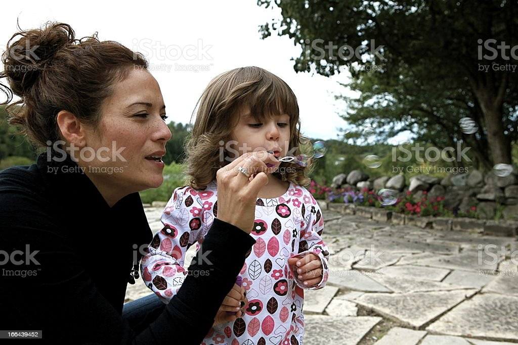 Mother and Child Blowing Bubbles in a Garden royalty-free stock photo