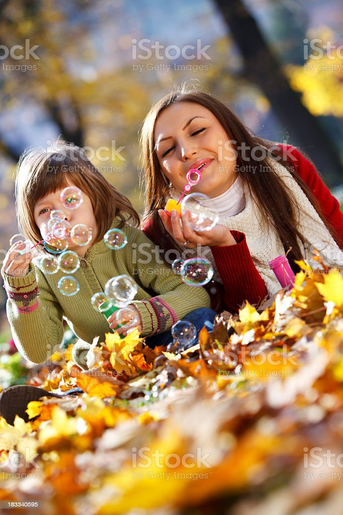 Mother and child blowing bubbles in nature stock photo