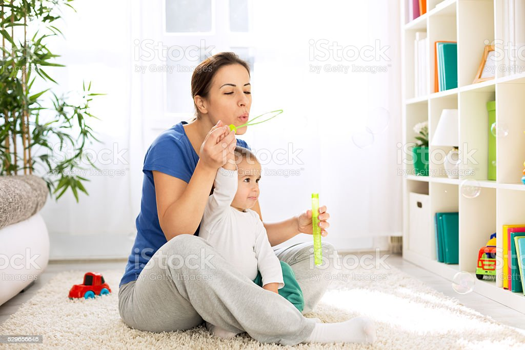 Mother and child blowing bubbles stock photo