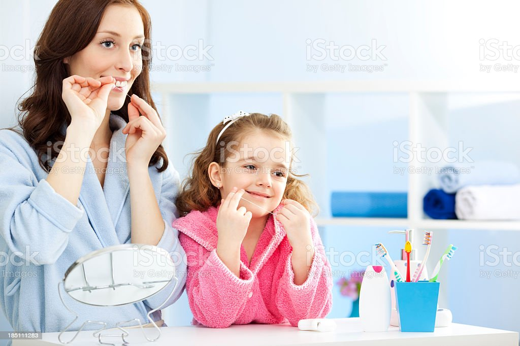 Mother and child dental flossing teeth together. stock photo