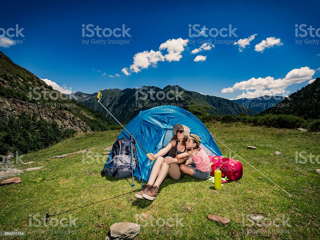 Mother and child doing a selfie photograph at camping tent stock photo