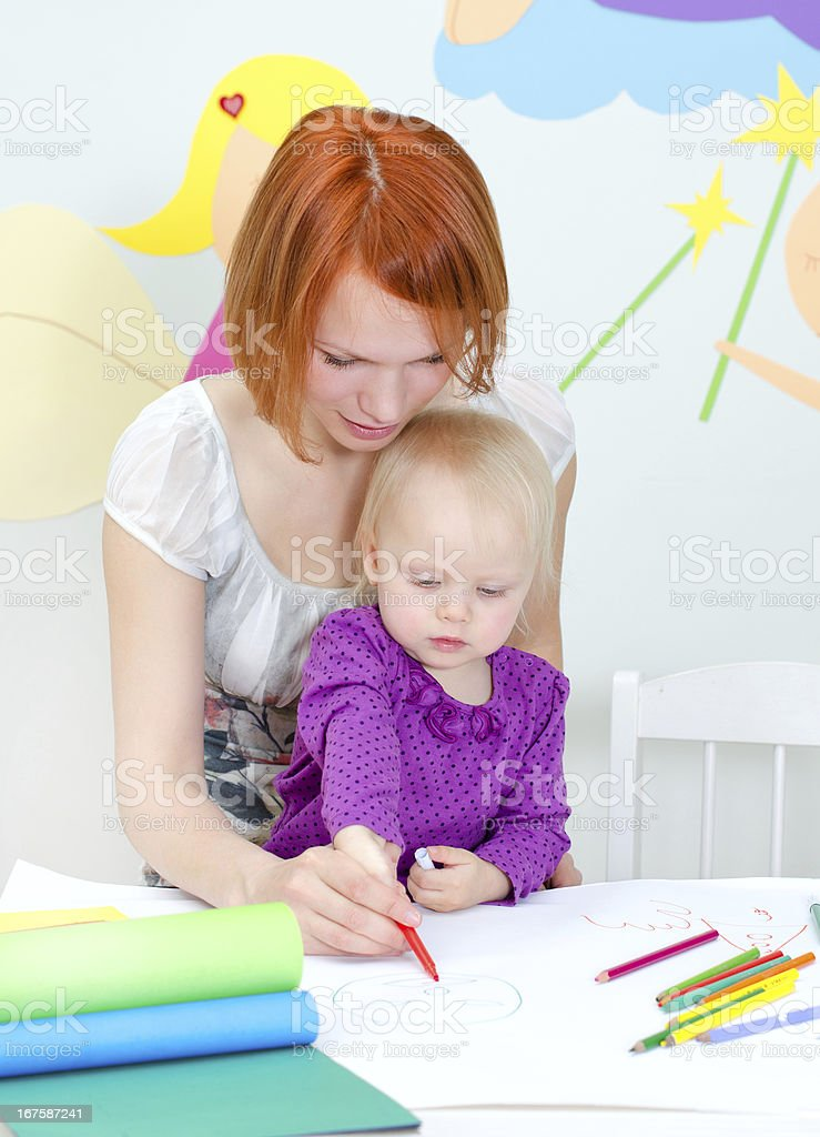 Mother and child drawing with color pencils stock photo