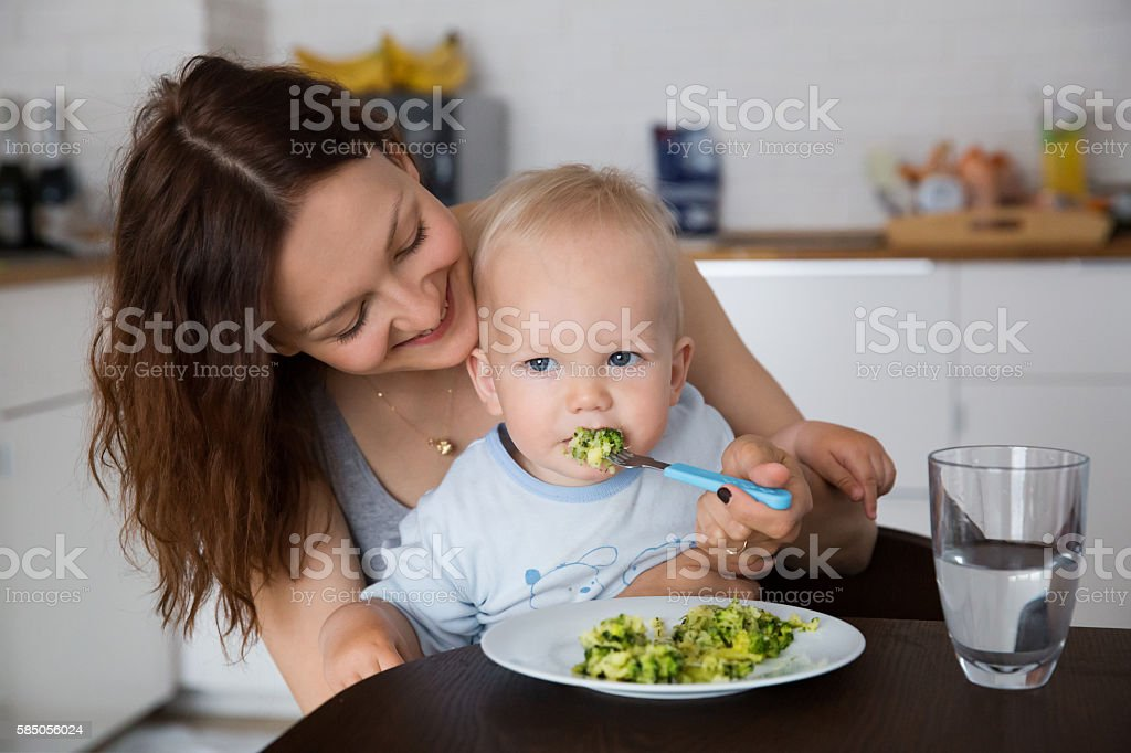 Mother and child eating together stock photo