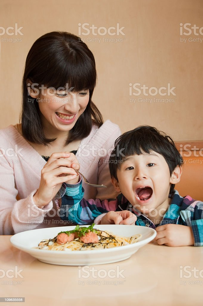 Mother and child enjoying a spaghetti meal together stock photo
