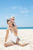 Mother and child in swimsuits at beach on sunny day