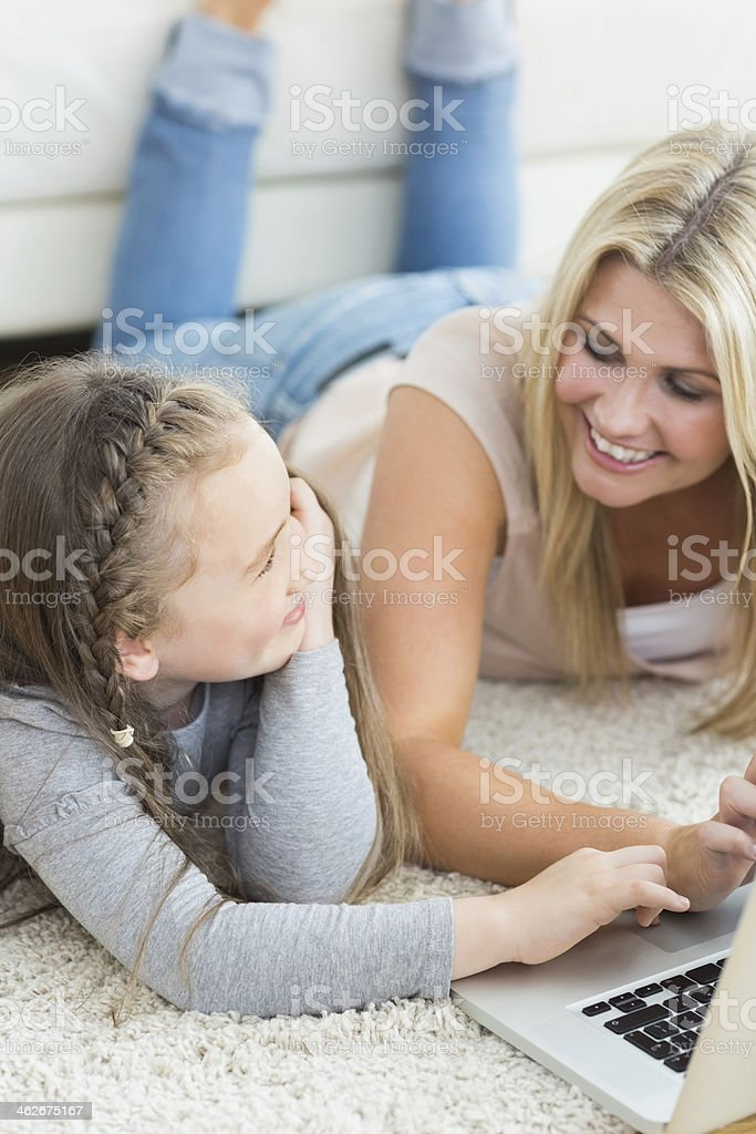 Mother and child lying on the floor smiling royalty-free stock photo
