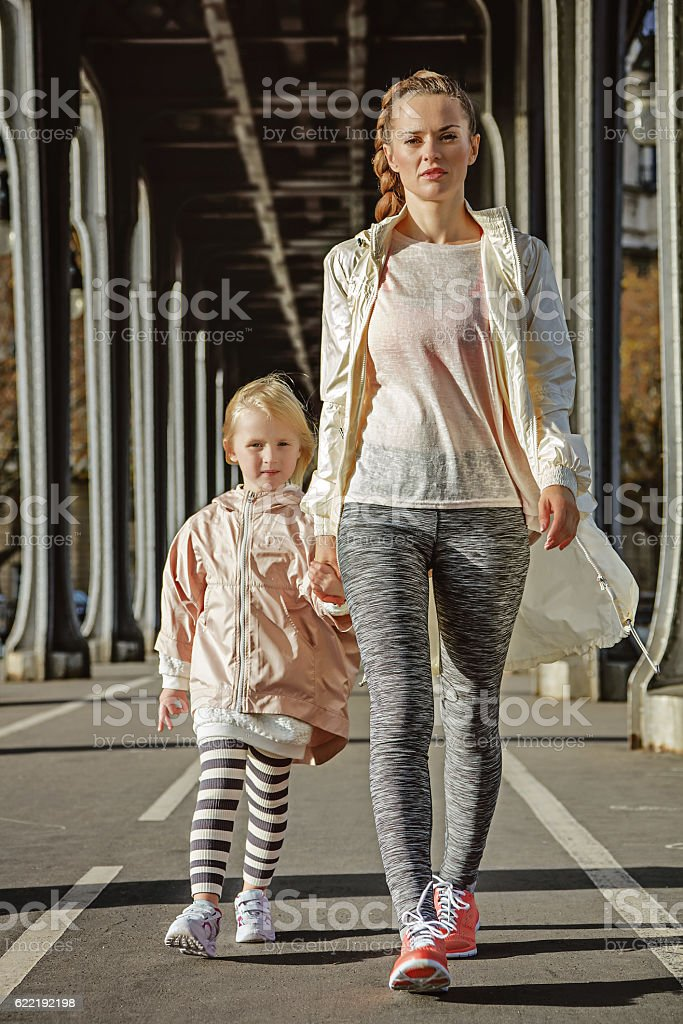 mother and child on Pont de Bir-Hakeim bridge going forward stock photo