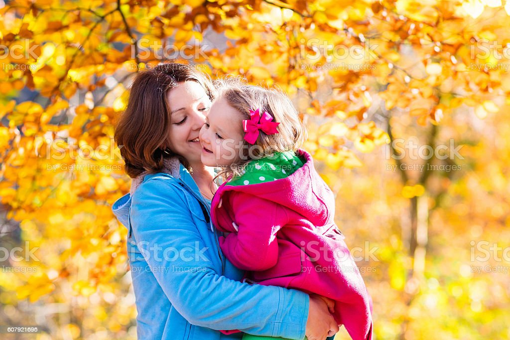 Mother and child playing in autumn park stock photo