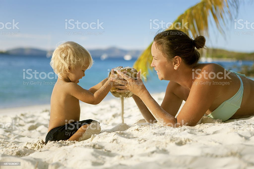mother and child playing with a coconut at the beach stock photo