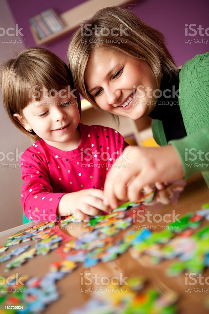 Mother and child playing with puzzle royalty-free stock photo