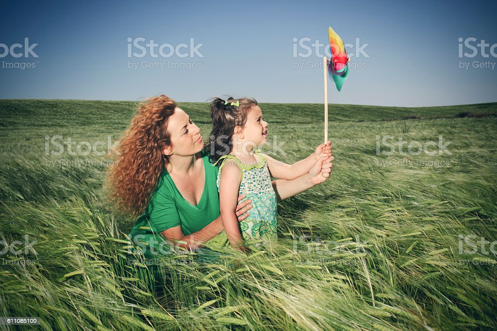 mother and child playing with toy windmill stock photo