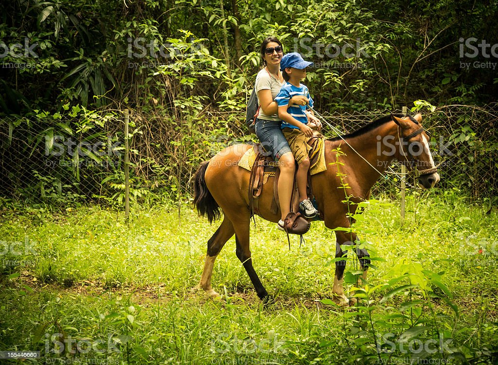 mother and child riding a horse royalty-free stock photo