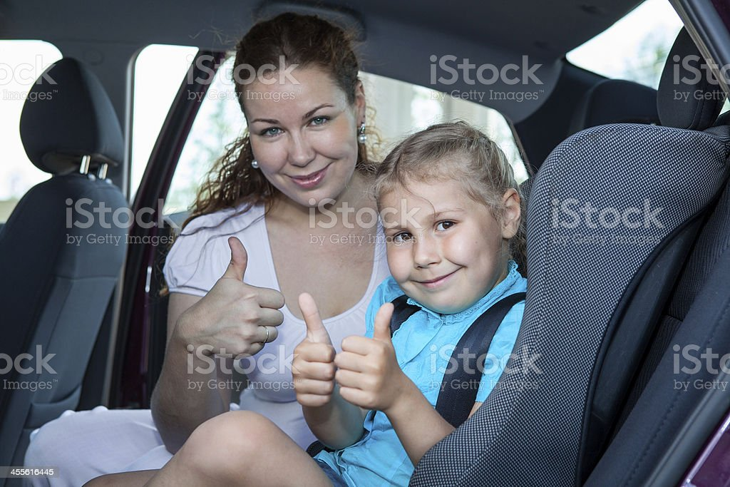 Mother and child showing thumb up gesture in car seat stock photo