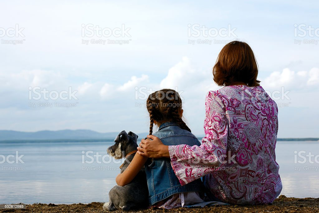 mother and child sitting embracing on the beach stock photo