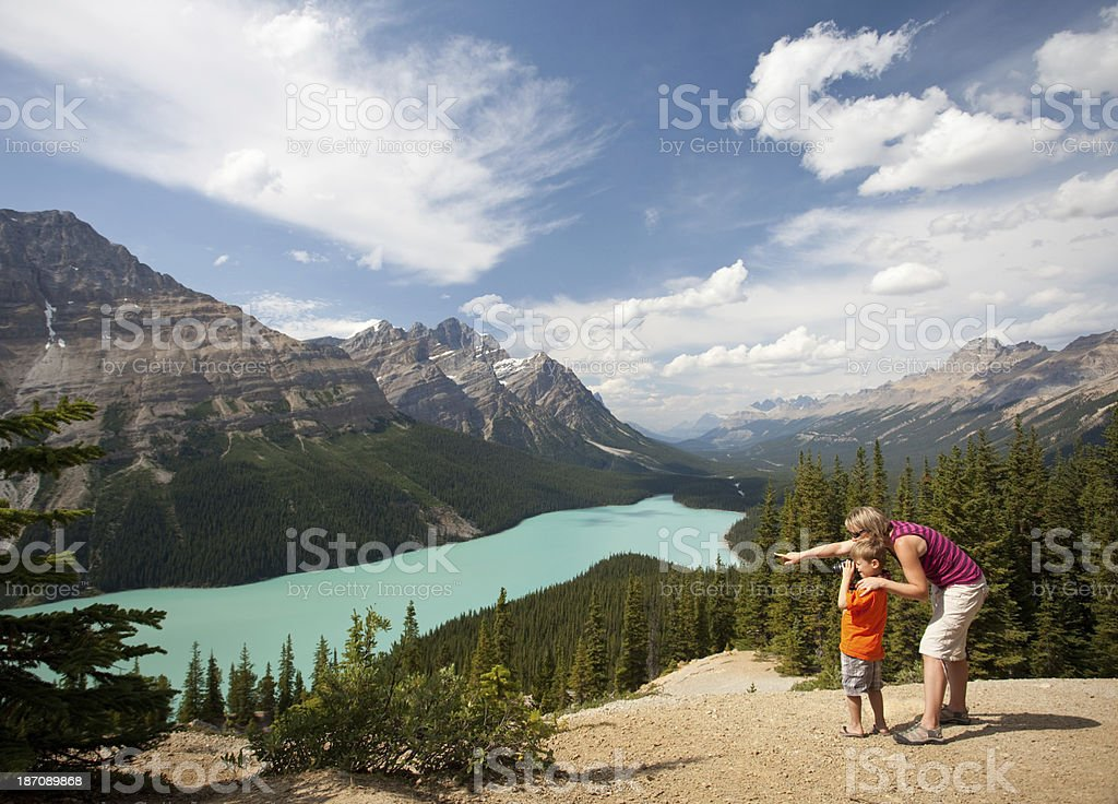 Mother and Child Taking Pictures at Beautiful Mountain Lake stock photo