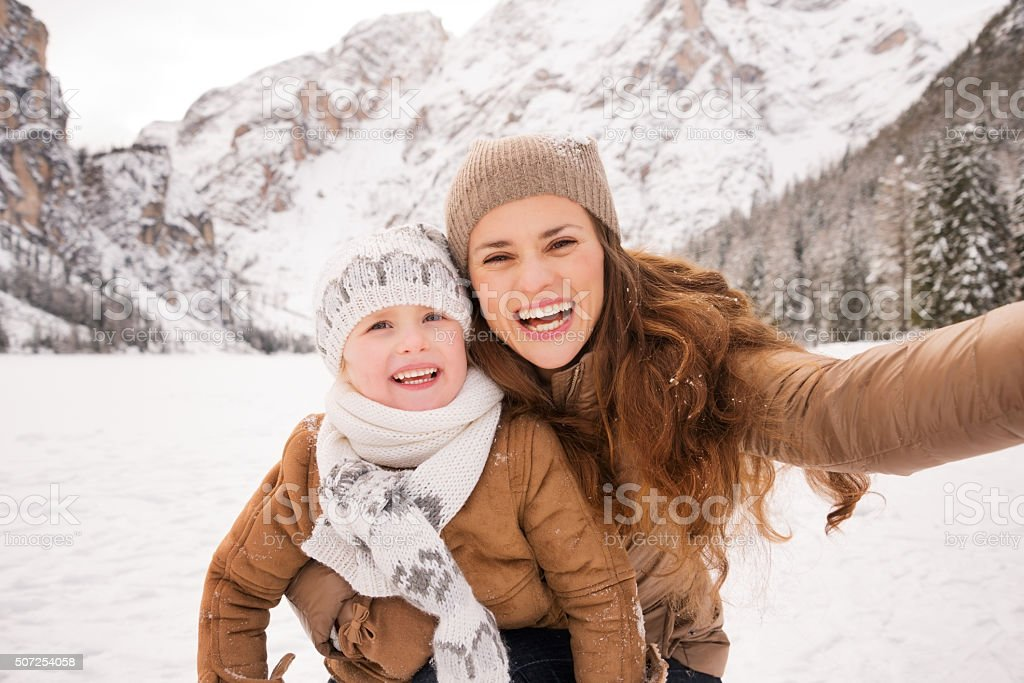 Mother and child taking selfie among snow-capped mountains stock photo