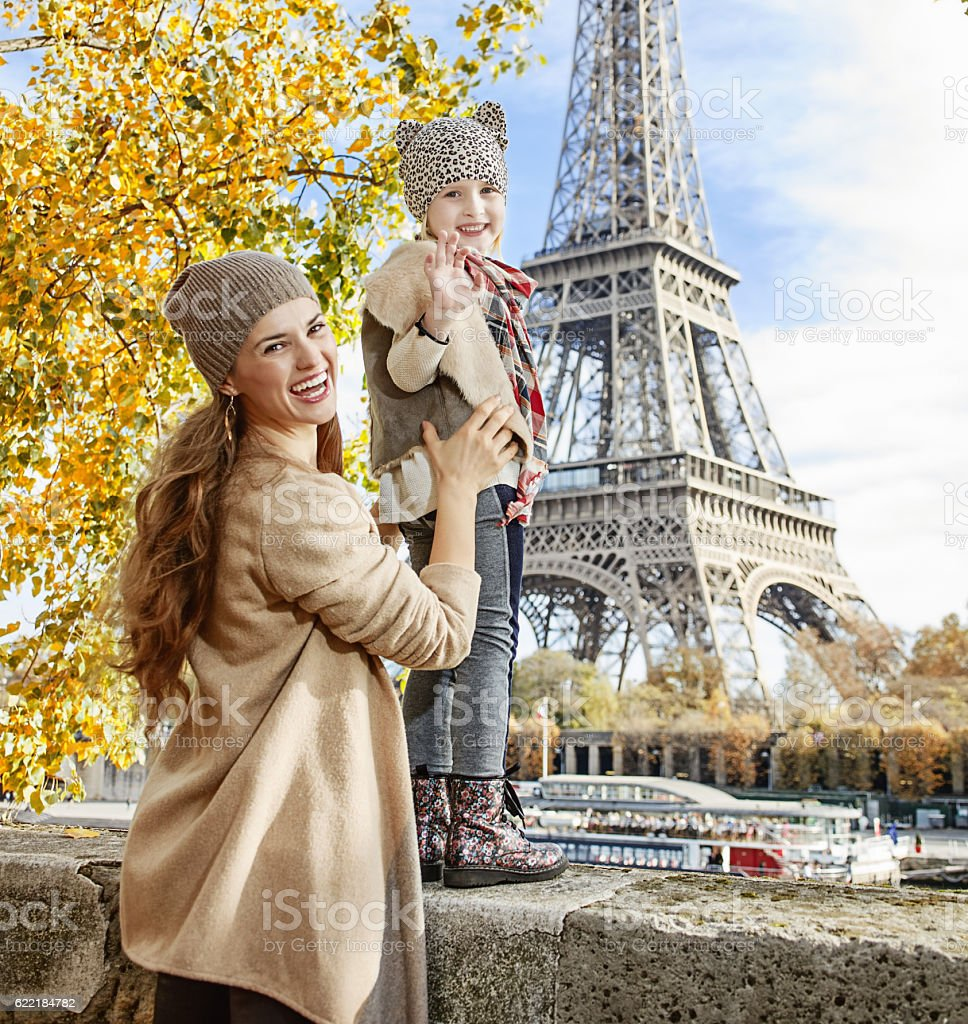 mother and child travelers handwaving on embankment in Paris stock photo