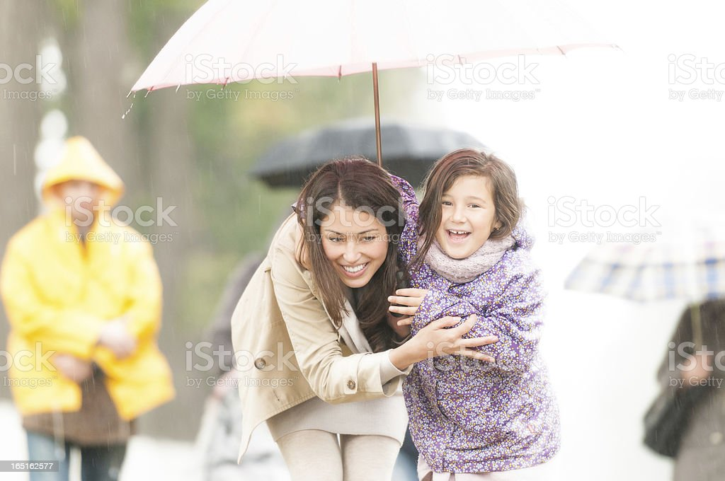 Mother and child under umbrella in rainy weather. stock photo