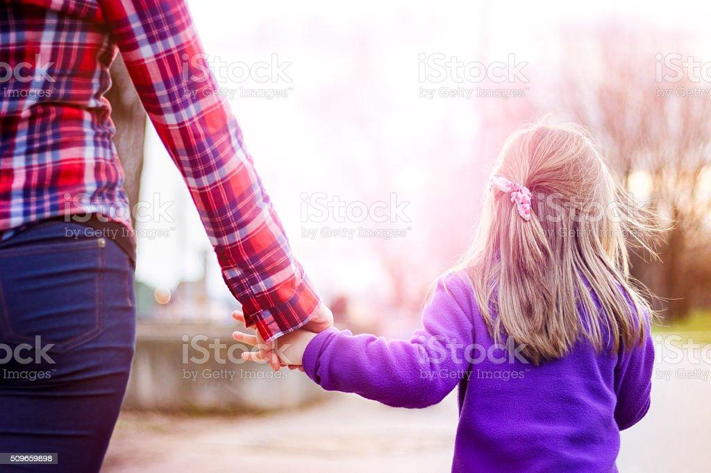 Mother and child walking and holding hands closeup stock photo